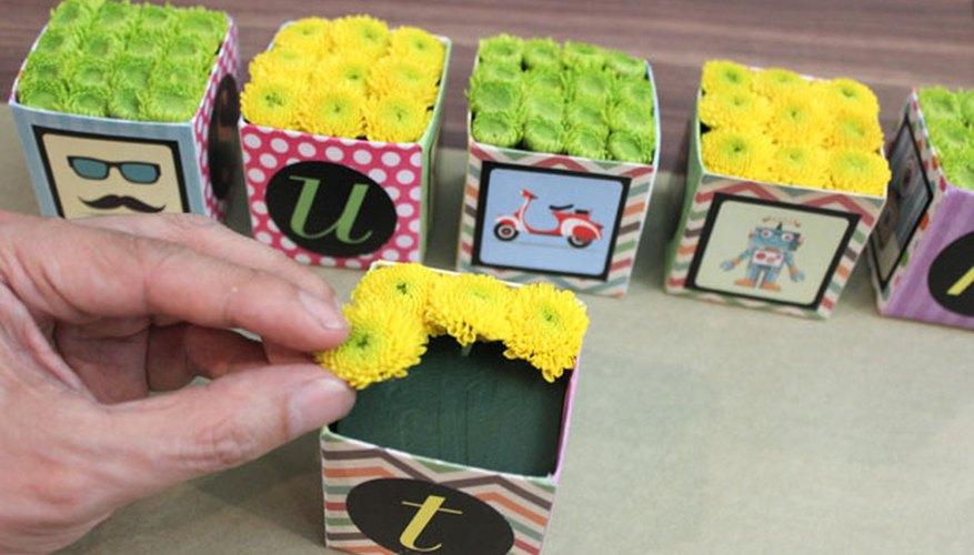 Inserta los crisantemos pompón en la espuma floral.