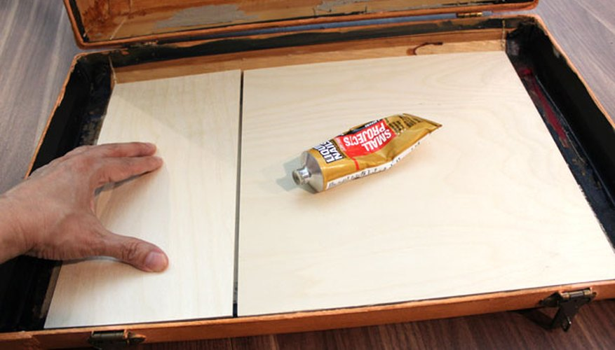 Adhiere una tabla de madera contrachapada al compartimiento.