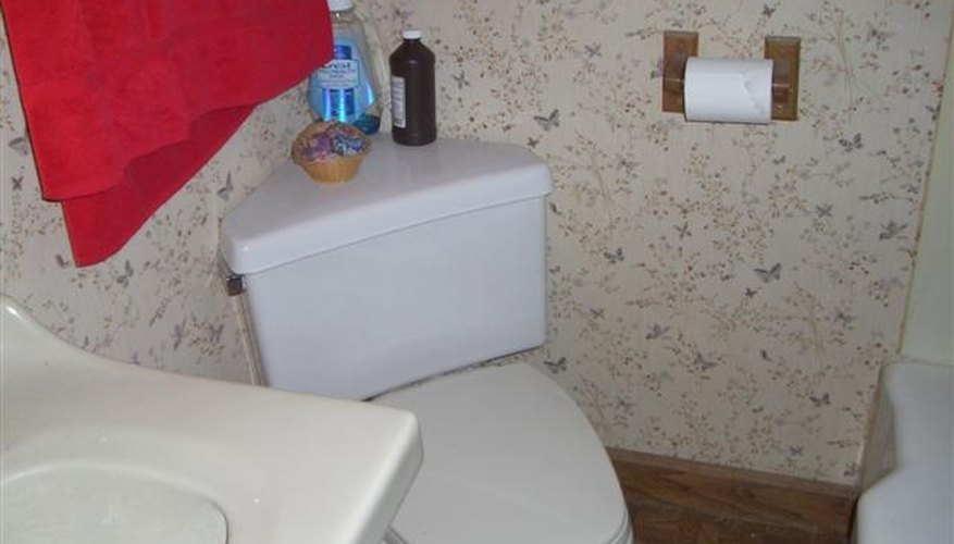 Before Remodel: Toilet, Vanity and Edge of Bathtub.