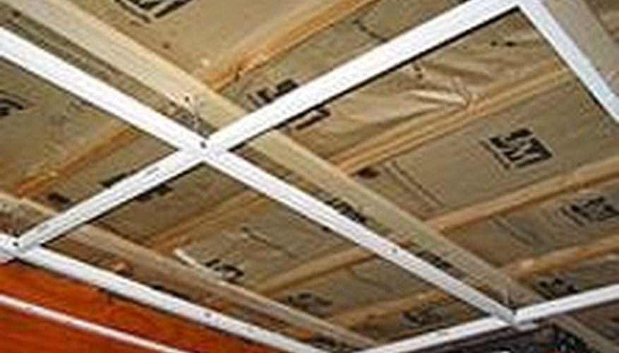 Hook the cross tees or cross runners 2 feet apart along the runners. If they donu0027t fit evenly leave a space around the outside. & How to Install a Drop Ceiling in Basement | HomeSteady