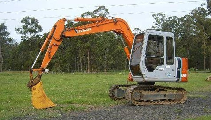 Use a small excavator like this one to begin tearing up the asphalt surface.