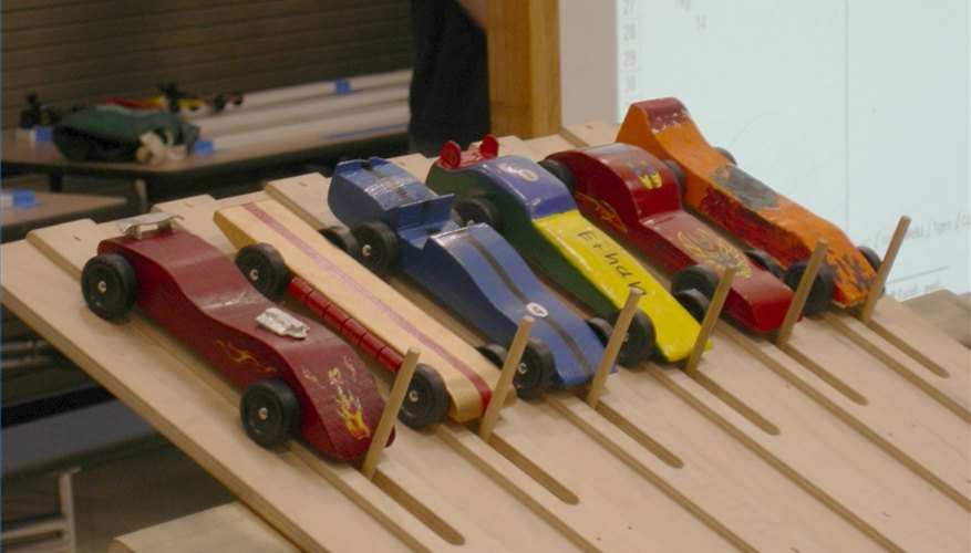 Pinewood derby cars sit at the starting gate.