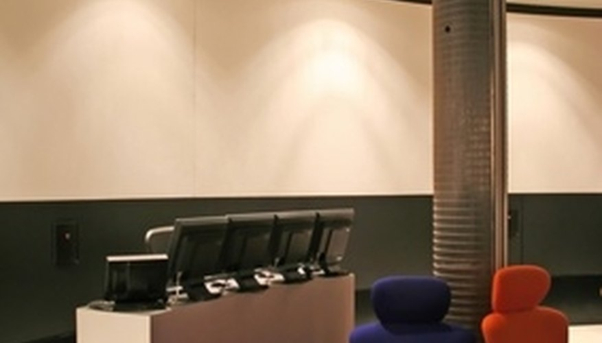 The receptionist desks is sleek and modern in black and white, surrounding by comfortable chairs.