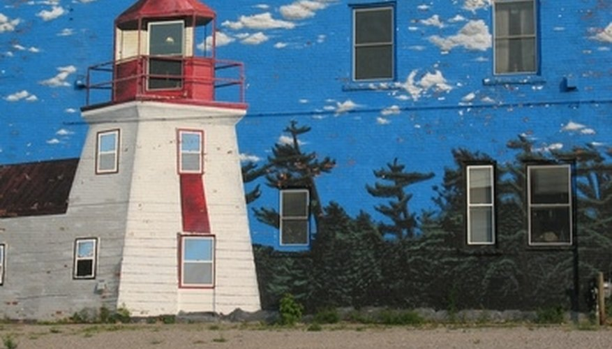 This wall mural gives the illusion of being on a beach near a lighthouse and forest.