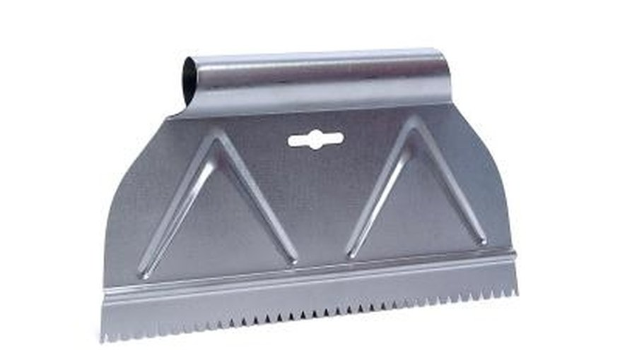 A metal scraper helps lift stuck-on adhesive.