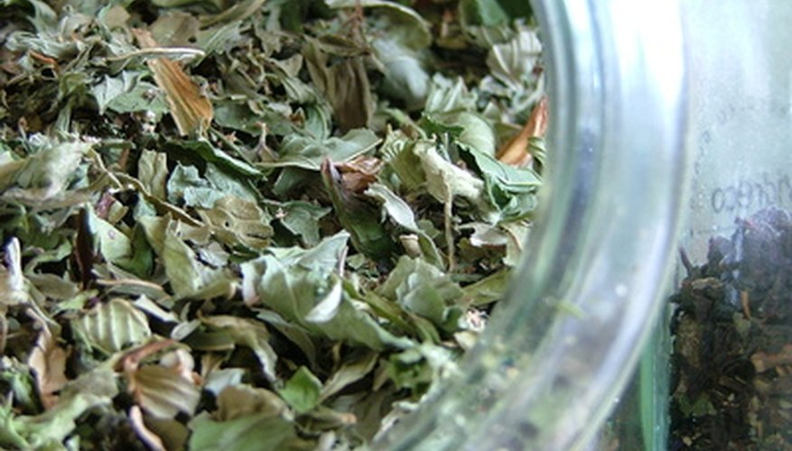 An open container of dried mint leaves releases mint fragrance.
