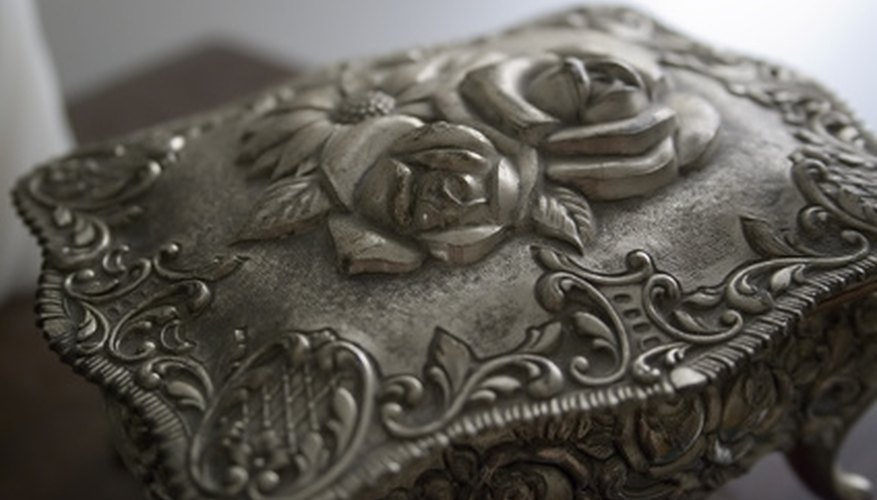 Pewter box has a rose design.