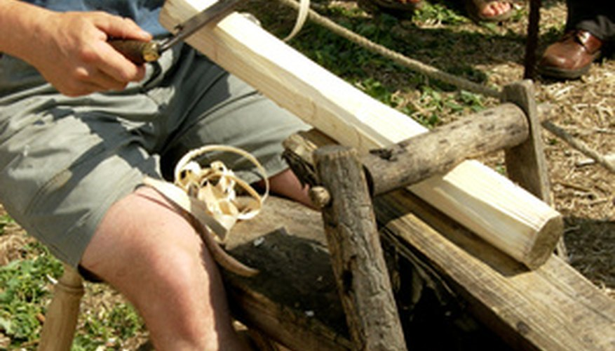 This man is using a froe to shape wood turned on a foot-powered lathe.