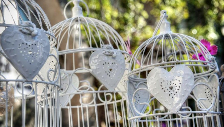White bird cages on an outdoor table.