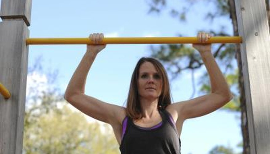 A woman is doing pullups outdoors.