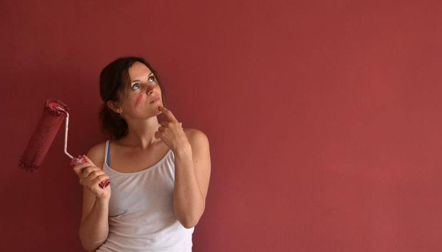 A woman holds a paint roller thinking in front of a red wall.