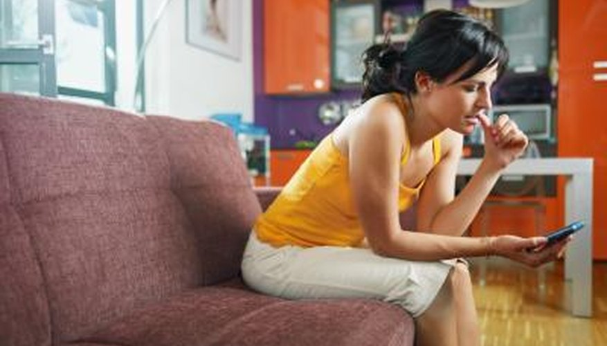 An apprehensive woman uses her cell phone in her apartment.
