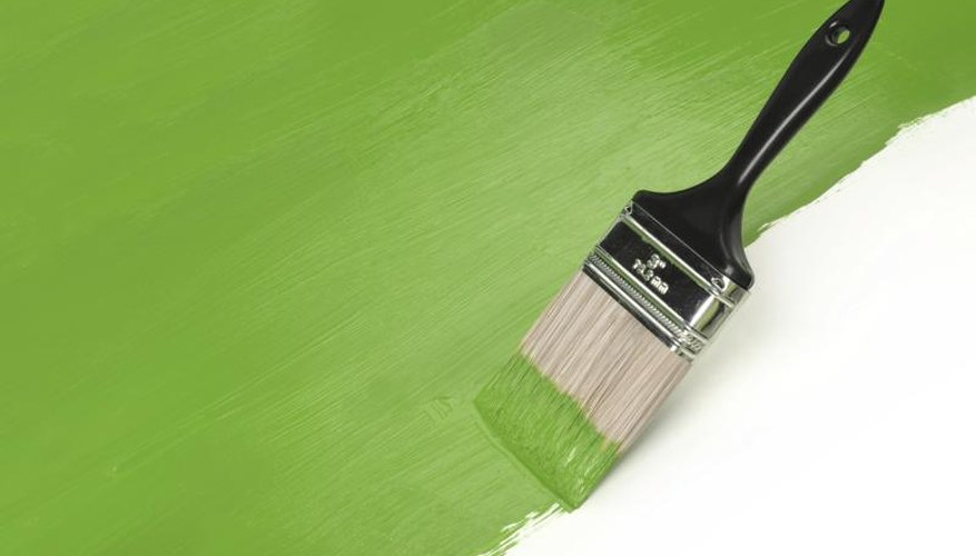 Paint brush spreading green paint on a white surface