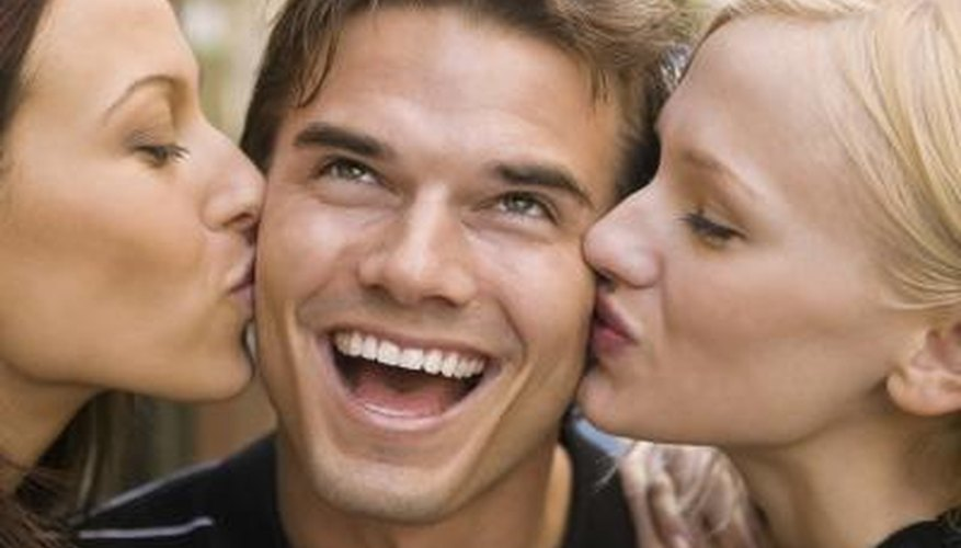 two woman giving a man playful kisses