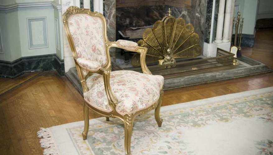 A chair painted gold in front of gold accessories on the hearth.