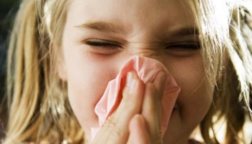 A close-up of a girl blowing her nose.