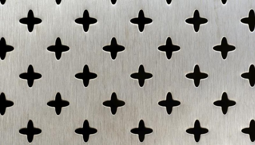 Close-up of a decorative perforated aluminum sheet, cut in a cross pattern.