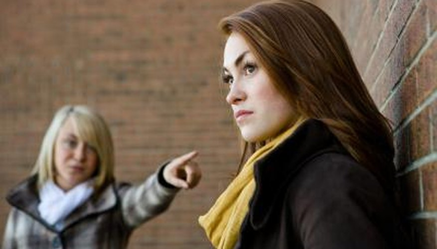 Teenage girls in argument, one points a finger at the other.
