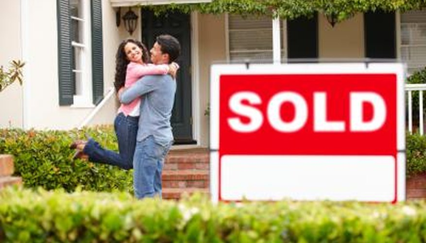 Couple hug in front of sold house