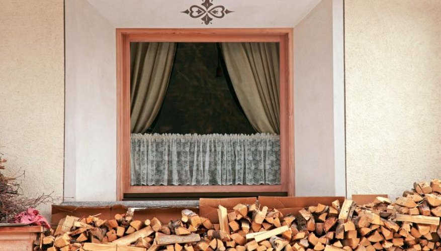 Cafe curtains inside the window above a wood pile.