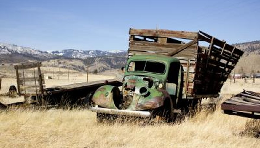 An old abandoned farm truck in a field.