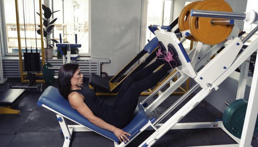 A woman perfoming leg repetitions on a machine.