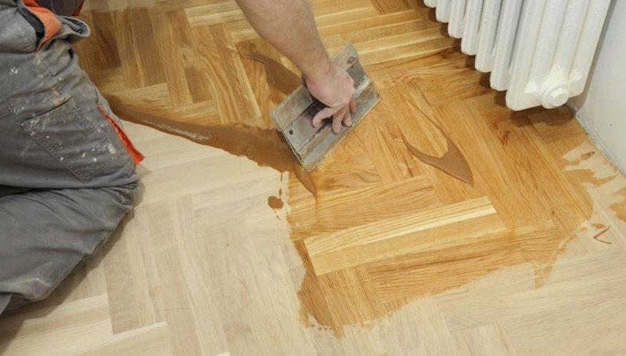 Worker varnishing oak floors