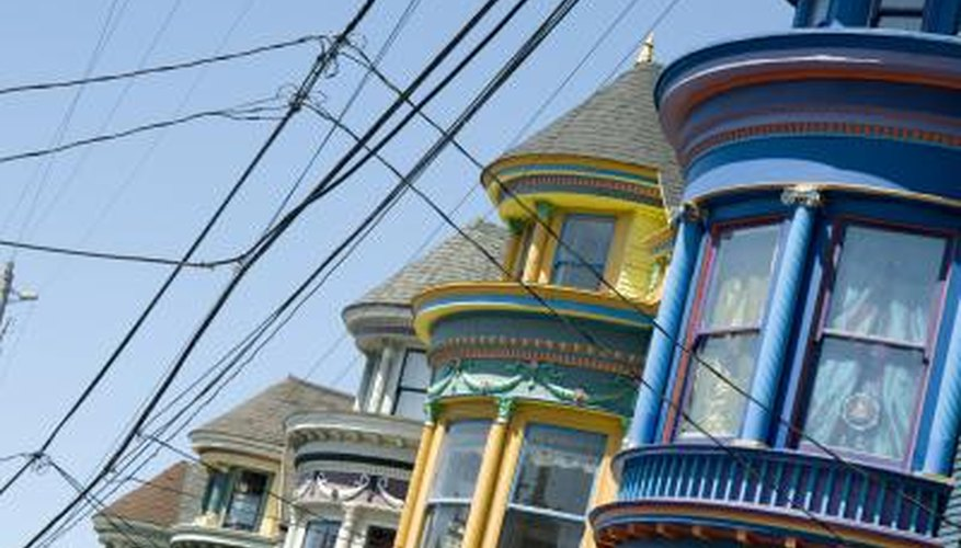 Cable car lines run by a blue Victorian with mauve trim around the windows.