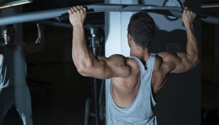 A young man is doing chin ups for his back and arm muscles.