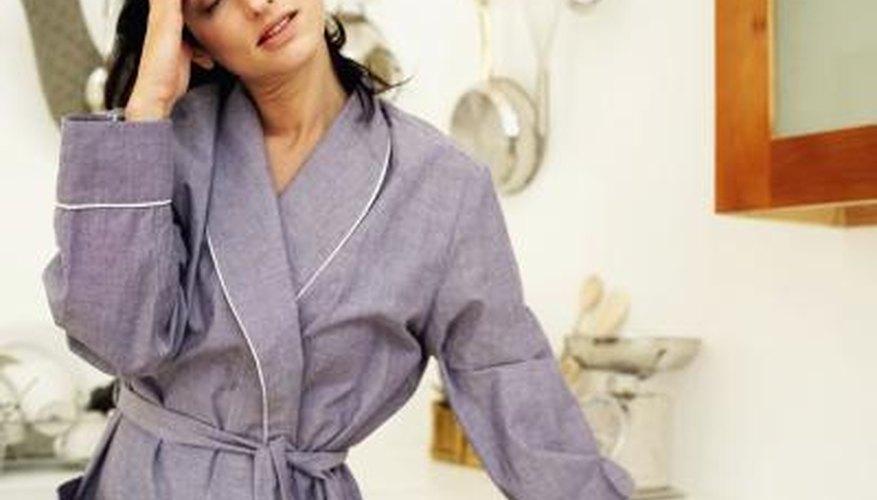 Woman wearing a robe, feeling dizzy.
