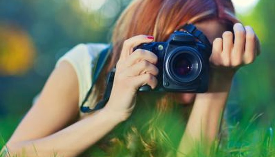 Young woman taking a picture with a camera outdoors.