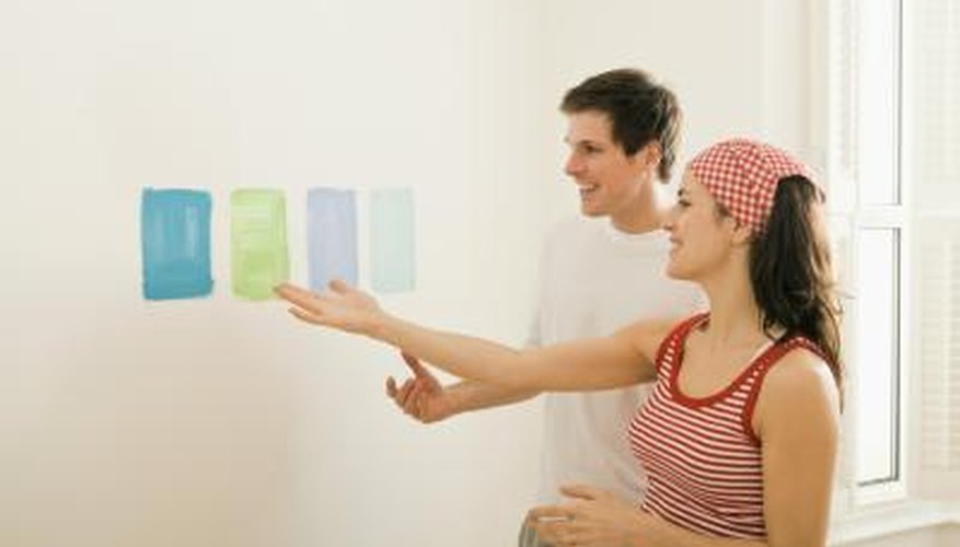 A couple compares paint samples on a white wall.