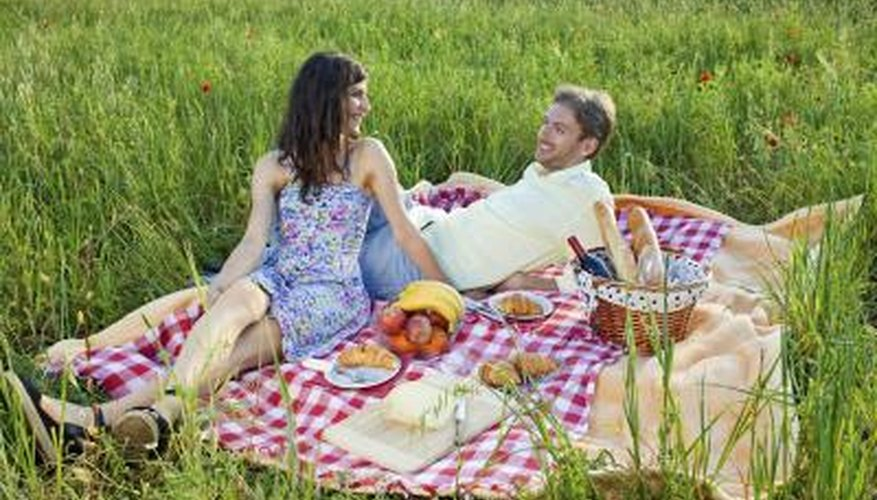Young couple picnicking in a field.
