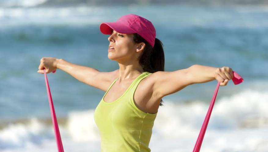 Young woman using a resistance band on the beach.