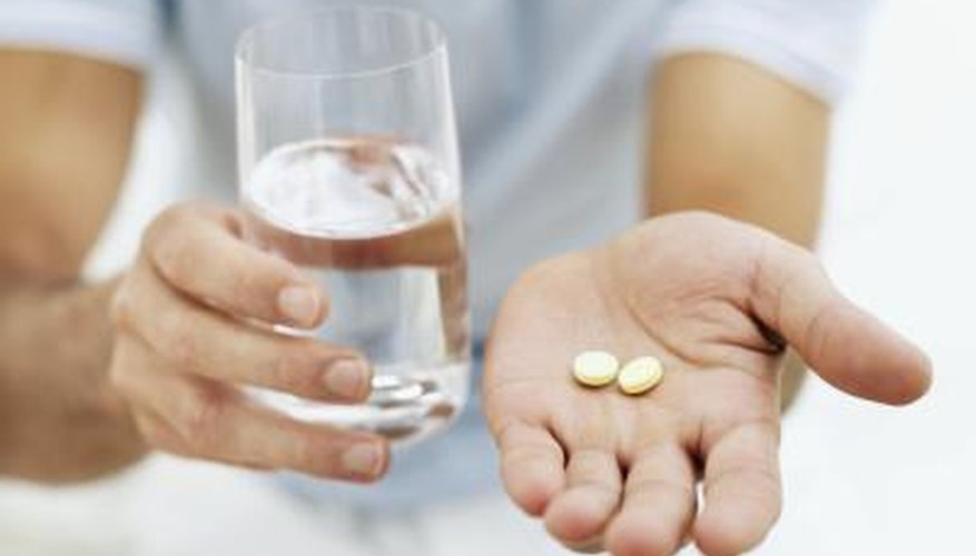 Man holding aspirin and a glass of water