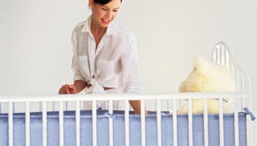Young mother looking over a standard crib.