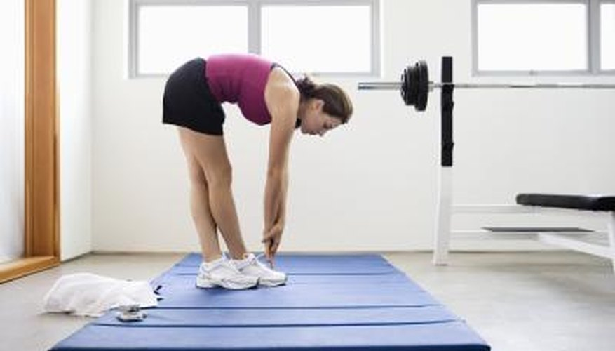Young woman doing stretches on a mat at the gym.
