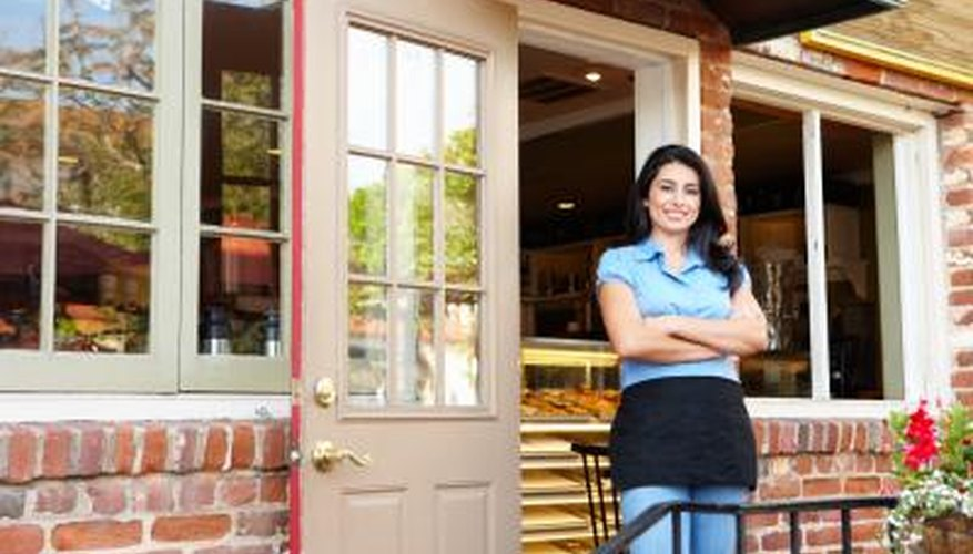 A small business owner stands in front of a bakery.