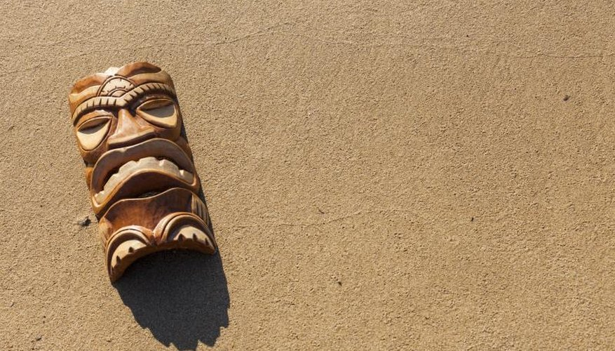 Tiki mask on sand.