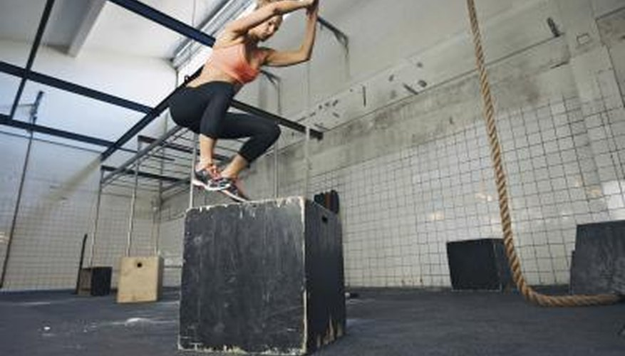 A woman performs plyometrics with a jump box.