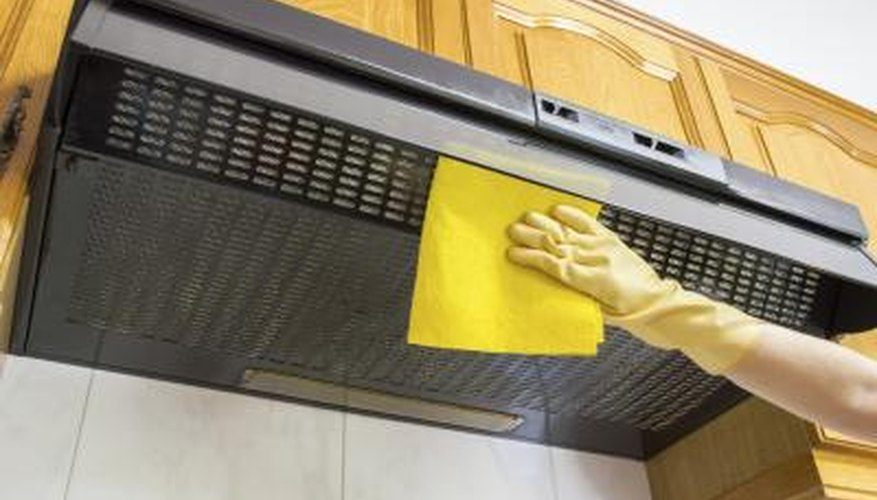 Ventilation hood for a gas stove top being cleaned.