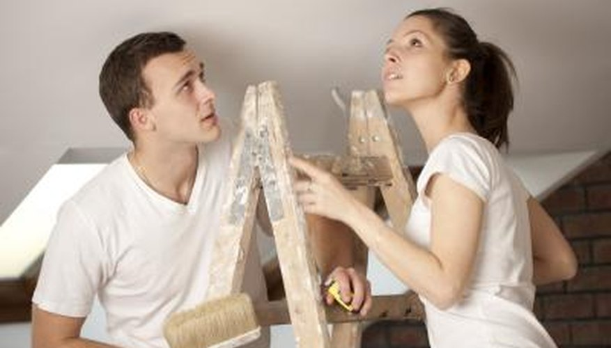 A couple on a ladder getting ready to paint a ceiling.