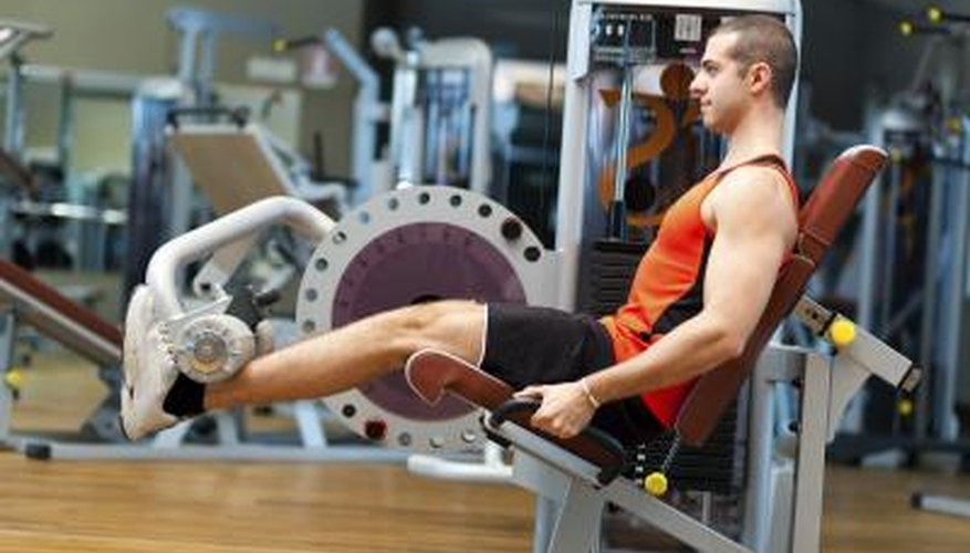 A man sitting in a machine at the gym to target the soleus.