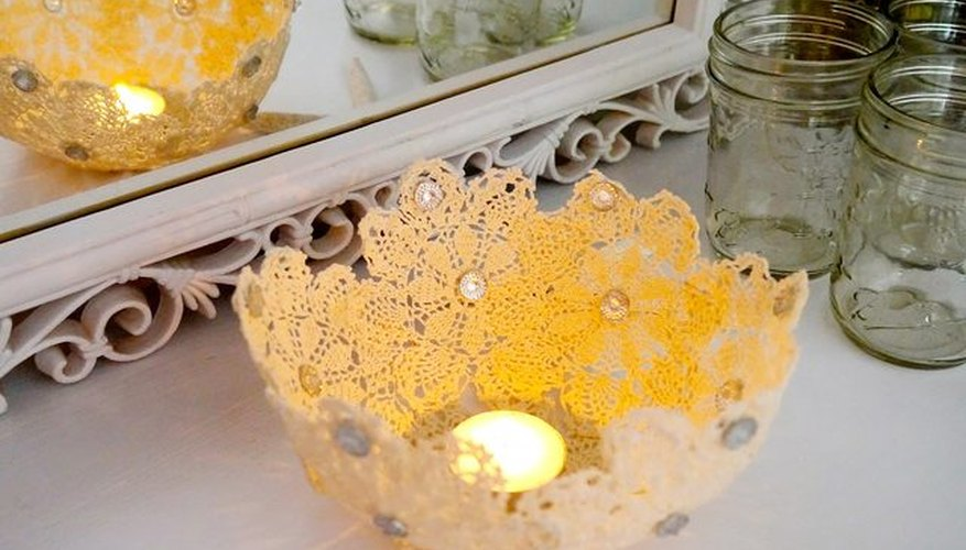 Smooth doilies around a balloon, paper mache style, to create a lacy candle holder.