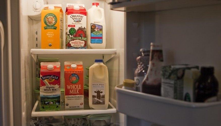 Botellas de leche ubicadas en el estante del medio de la heladera