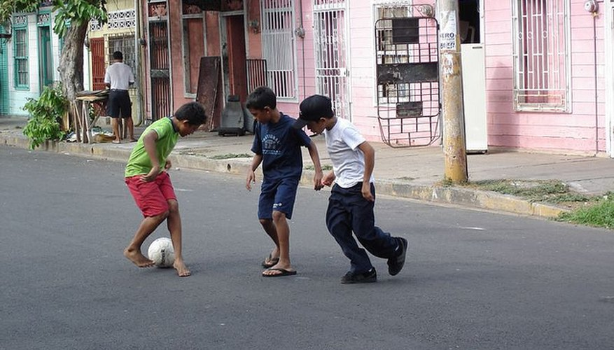 Niños jugando a la pelota en la calle