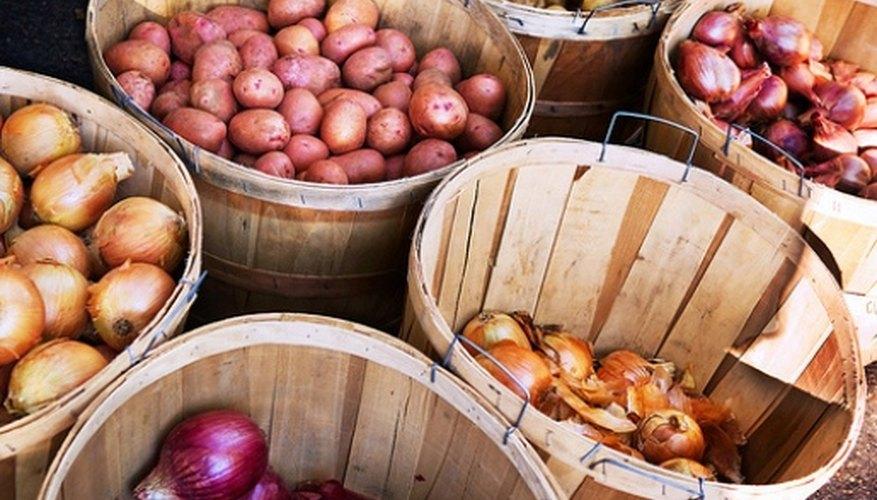 Papas y cebollas almacenadas en contenedores de maderas