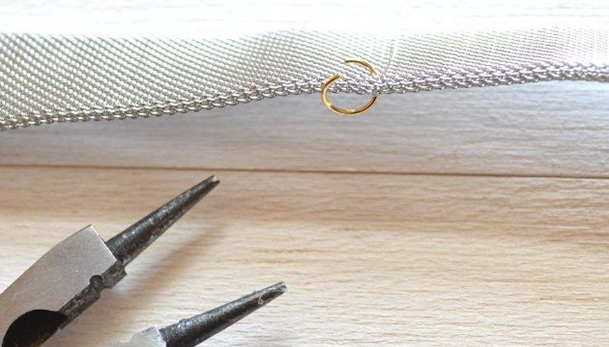 Desliza cuidadosamente el anillo del salto a través de la cadena de malla.