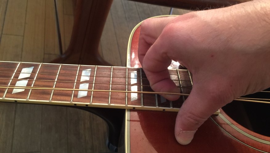 Stretch out strings by gently pulling at 12th fret.