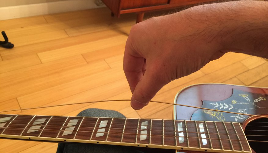 Pull string 4-5 inches above 12th fret to create slack.